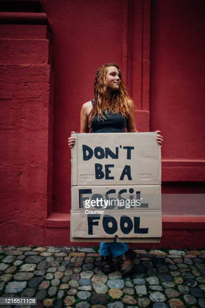 teenage girl holding climate school strike protest sign - march stock-fotos und bilder