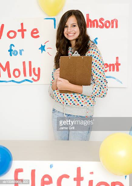 Teenage girl (14-15) holding clipboard running for president election, smiling, portrait