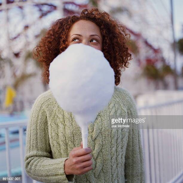 Teenage girl (16-18) holding cotton candy in amusement park