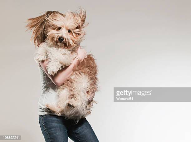 Teenage girl (16-17) holding dog and jumping