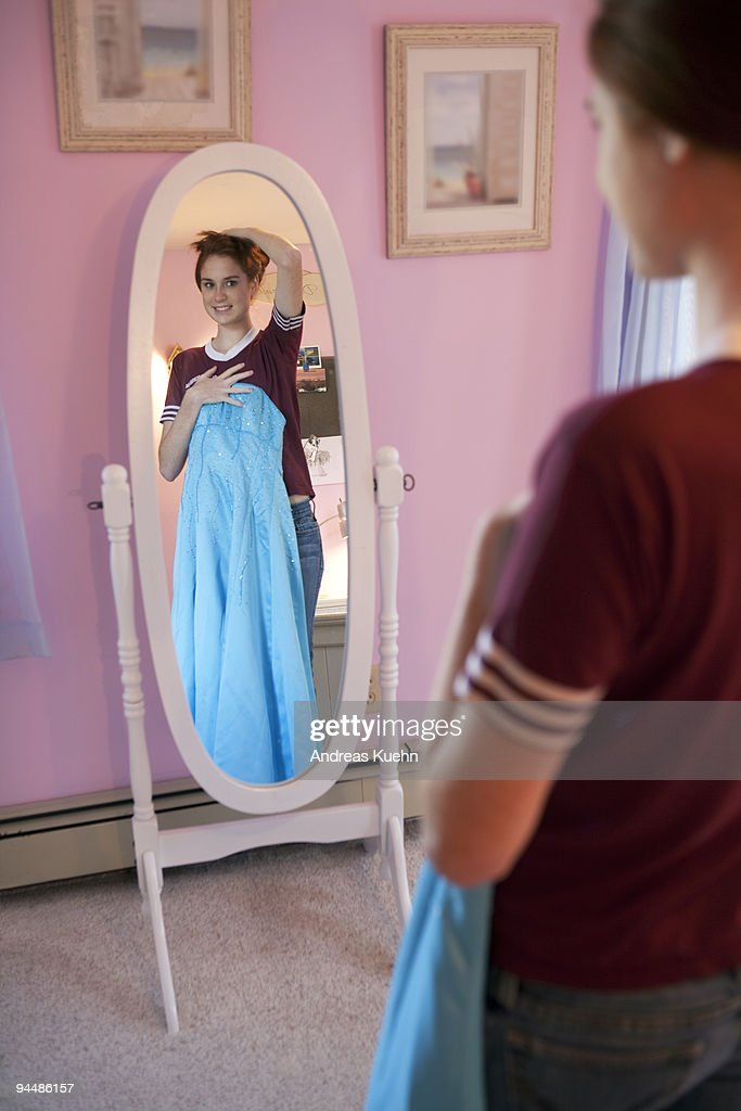 Teenage girl holding dress in front of mirror. : Stock Photo