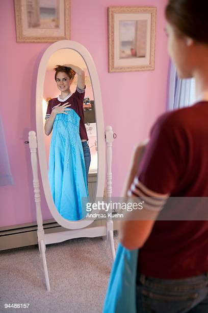 Teenage girl holding dress in front of mirror.
