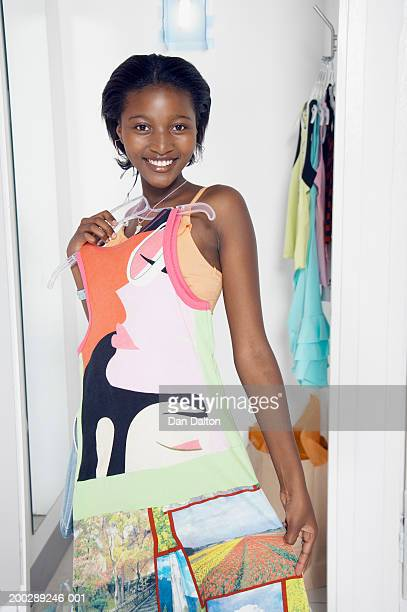 Teenage girl (14-16) holding dress on hanger in change room, portrait