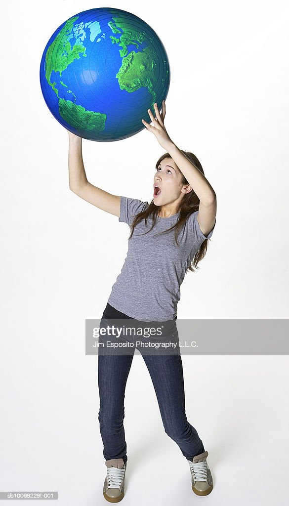 Teenage girl (16-17) holding globe over her head : Stockfoto
