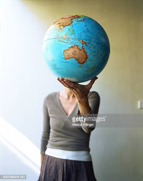 teenage girl (15-17) holding globe (focus on australia) - obscured face stock pictures, royalty-free photos & images
