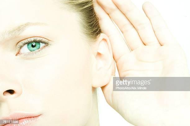 'Teenage girl holding hand behind ear, looking at camera, close-up'