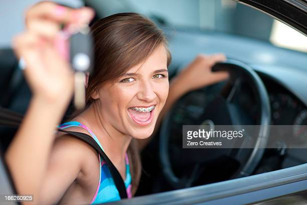 Teenage girl holding keys to new car