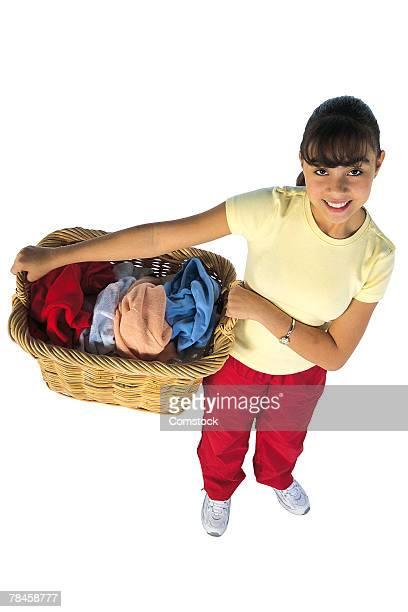 Teenage girl holding laundry basket