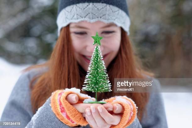 Teenage girl holding little Christmas tree