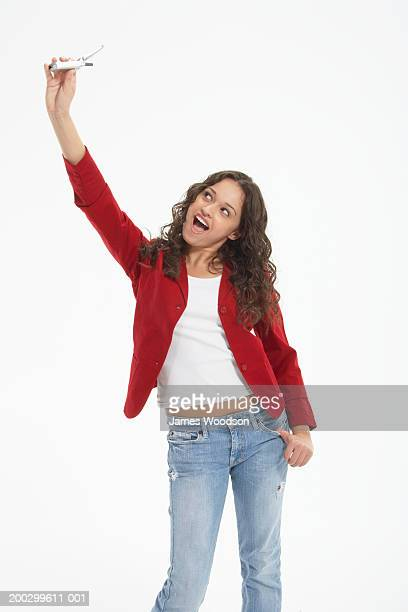 teenage girl (15-17) holding mobile phone in the air, mouth open - girls open mouth stock photos and pictures