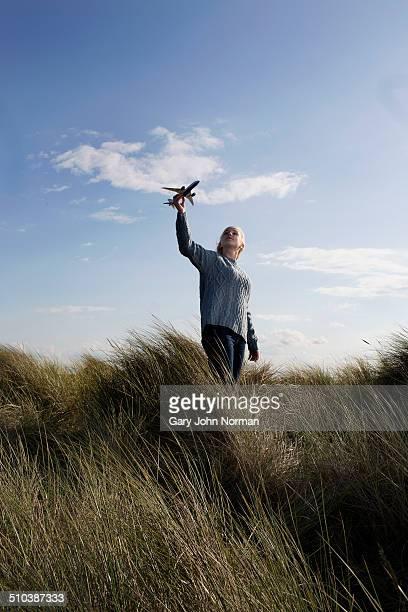 Teenage girl holding model aeroplane