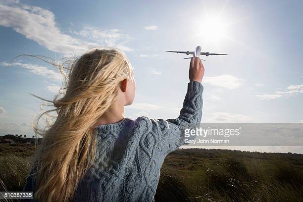 Teenage girl holding model aeroplane