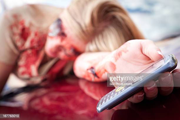 teenage girl holding out cell phone on car after wreck - dead female bodies stockfoto's en -beelden