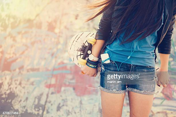 Teenage girl holding skateboard
