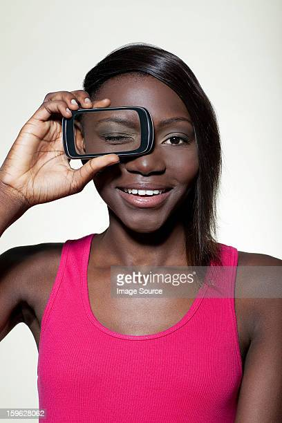 Teenage girl holding smartphone over eye