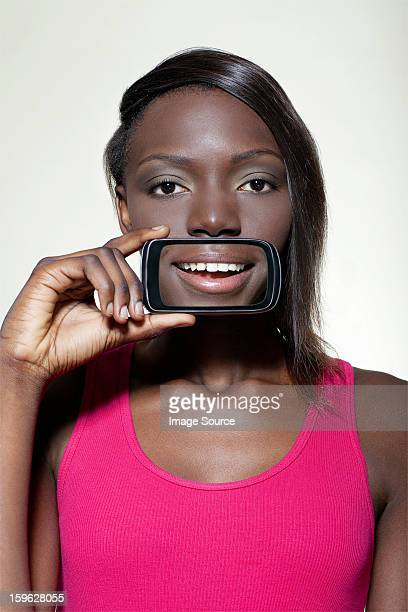 Teenage girl holding smartphone over mouth