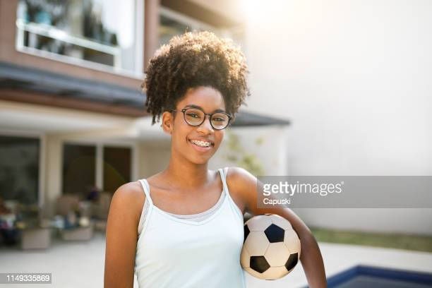 teenage girl holding soccer ball - female high school student stock pictures, royalty-free photos & images