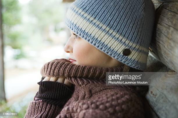 Teenage girl holding sweater neck over chin, side view, close-up