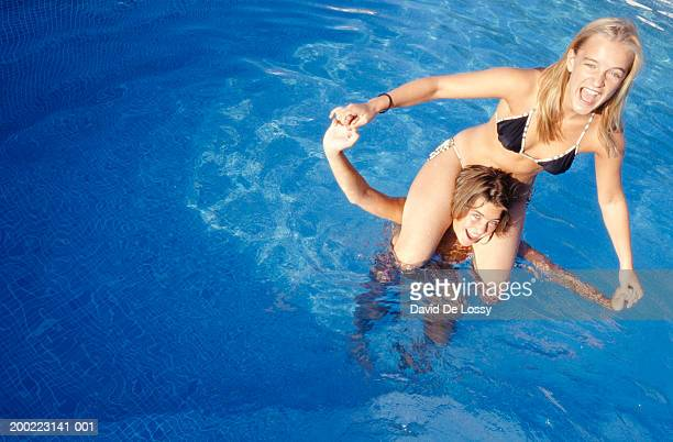 teenage girl (16-17) holding teenage girl (16-17) on shoulders in pool, elevated view - carrying a person on shoulders stock photos and pictures