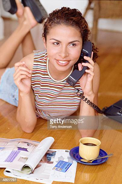 Teenage girl (16-18) holding telephone, ordering from catalog