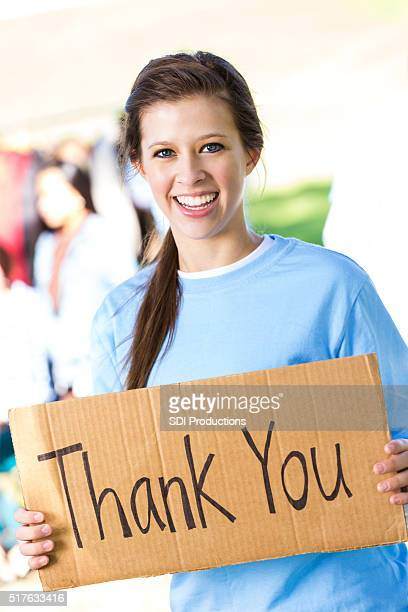 Teenage girl holding 'Thank You' sign at clothing drive