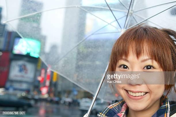 Teenage girl (16-18) holding umbrella, smiling, portrait, close up