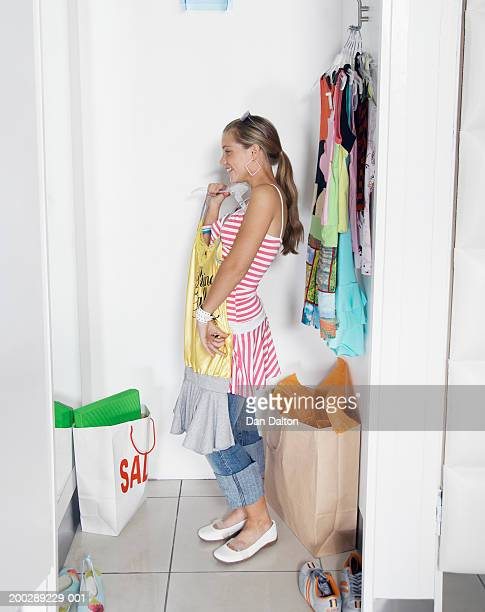 Teenage girl (13-15) holding up dress on hanger in change room of shop
