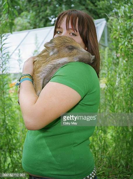 Teenage girl (14-16) holding young wild boar, portrait