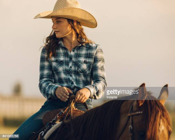 A teenage girl horseback riding by herself at sunset.
