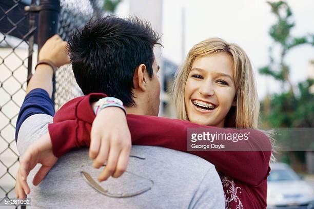 Teenage girl hugging a Teenage boy