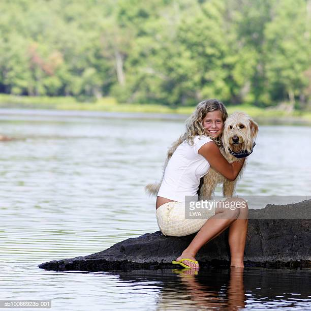 teenage girl (14-15 years) hugging dog at lake's edge - 14 15 years stock pictures, royalty-free photos & images