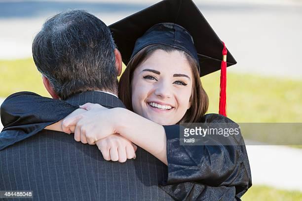 Teenage girl hugging father wearing graduation gown