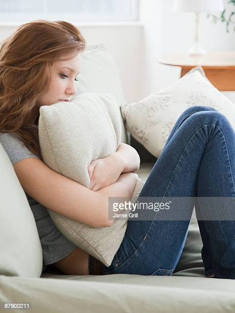 Teenage girl hugging pillow, unhappy