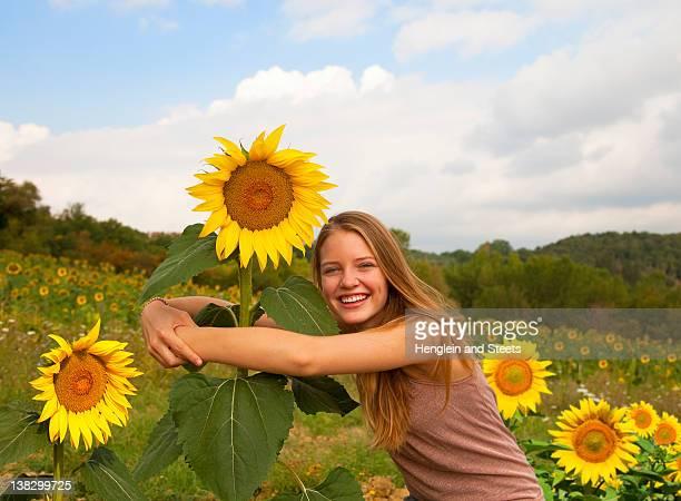 teenage girl hugging sunflower in field - landbouwgrond stockfoto's en -beelden
