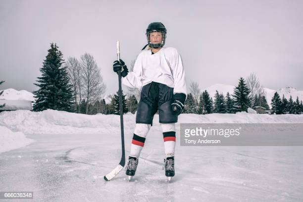 Teenage girl ice hockey player standing on outdoor rink in winter