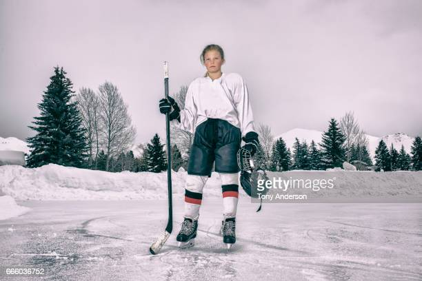 teenage girl ice hockey player standing on outdoor rink in winter - hockey player stock pictures, royalty-free photos & images
