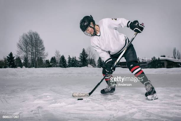 teenage girl ice hockey player taking a shot on outdoor rink in winter - ice hockey rink stock pictures, royalty-free photos & images
