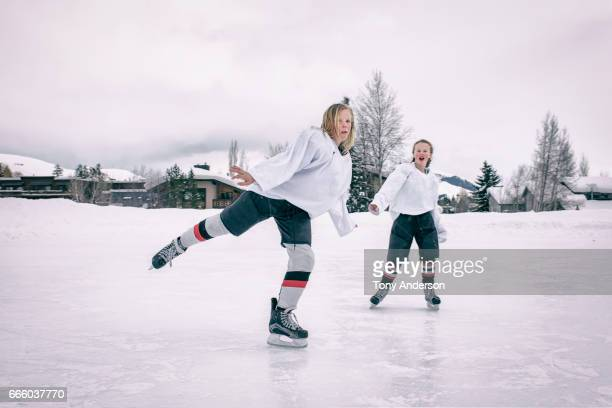 Teenage girl ice hockey players playing around on outdoor rink in winter