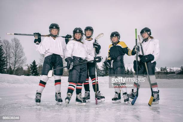 teenage girl ice hockey players standing on outdoor rink in winter - ice hockey stock pictures, royalty-free photos & images