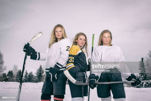 Teenage girl ice hockey players standing on outdoor rink in winter
