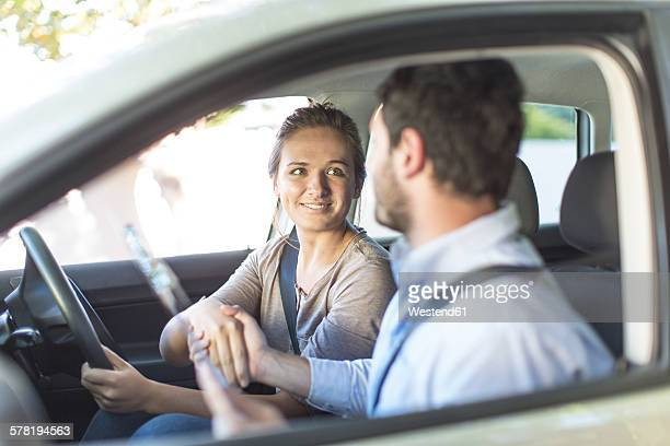 Teenage girl in a car shaking hanbds with driving inspector