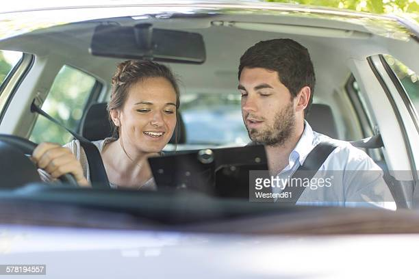Teenage girl in a car with driving instructor