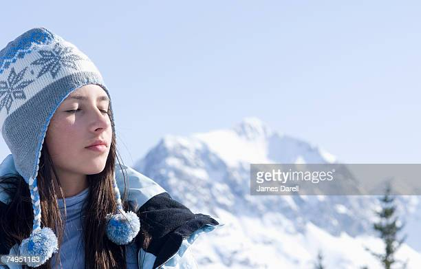 Teenage girl (14-15) in alpine landscape, with eyes closed, close-up