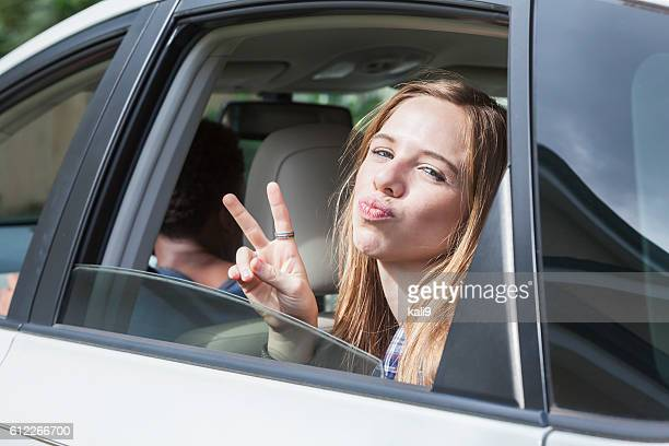 teenage girl in back seat of car making peace sign - girls open mouth stockfoto's en -beelden