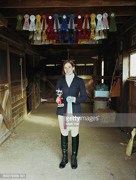 Teenage girl (17-19) in barn holding trophy and prize ribbon, portrait