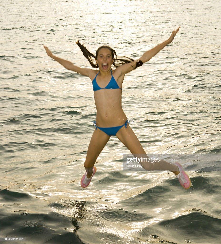 Teenage girl (13-14) in bikini jumping into water : Stock Photo