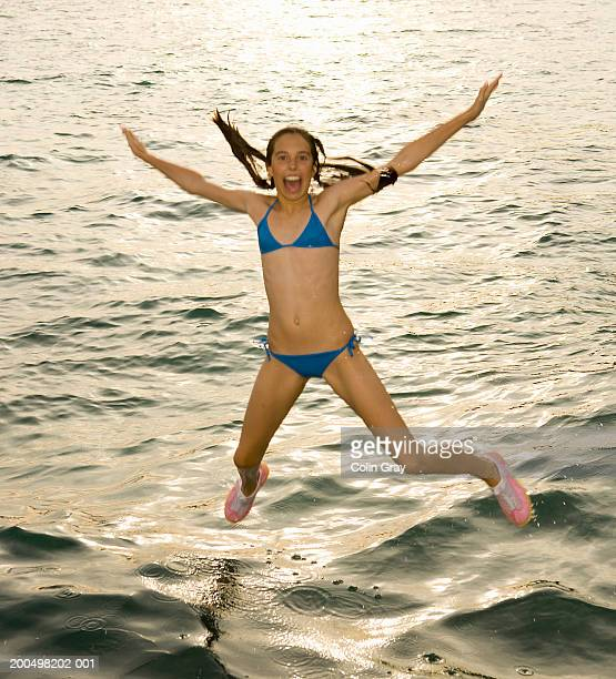 teenage girl (13-14) in bikini jumping into water - legs apart stock photos and pictures