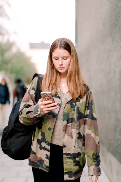 Teenage girl in camouflage shirt using smart phone while walking on footpath