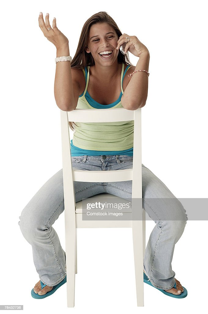 Teenage girl in chair talking on cell phone : Stockfoto