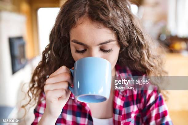 一杯のコーヒーを楽しんでいるチェックのシャツで十代の少女